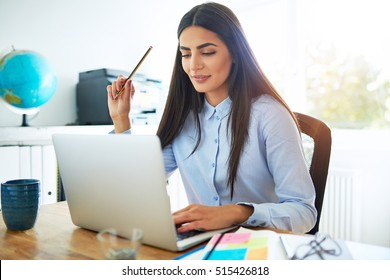Single calm young Indian woman in blue blouse and long hair holding pencil in hand while seated at desk in front of laptop computer in bright room
