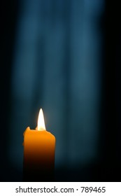 single candle with blurred out dawn through curtains window