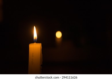 Single candle burning at night with bokeh defocused background