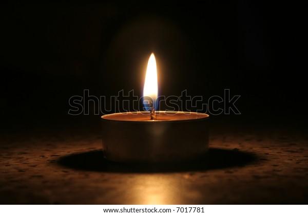 Single candle in dark in portrait