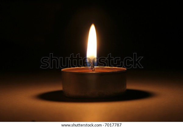 Single candle in dark in portrait