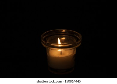 Single candle in a glass jar