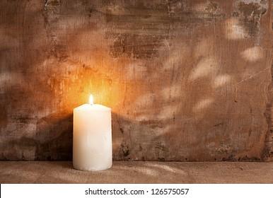 single candle light on grunge background.still life