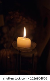 Single candle on the glass stand with shadow dark background
