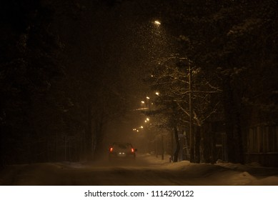 Single car on a road in the evening. Heavy snowfall is illuminated by street lamps.