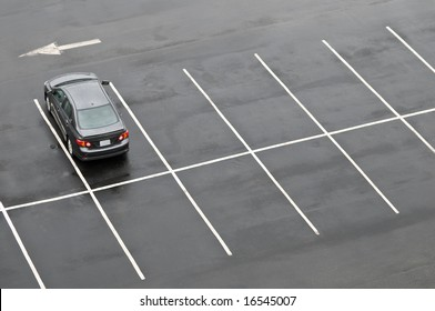 Single car in otherwise empty parking lot, in the rain