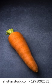 single carrot, a root vegetable isolated on a dark textured background