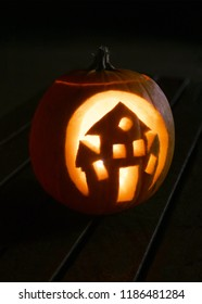 single carved pumpkin for halloween with a haunted house cut out vertical for posters and copy space