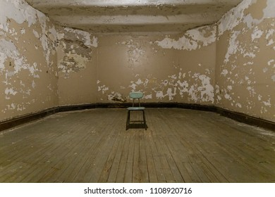 Single chair sitting in a room with peeling paint