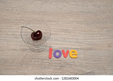 A single cherry in a glass bowl with the word love
