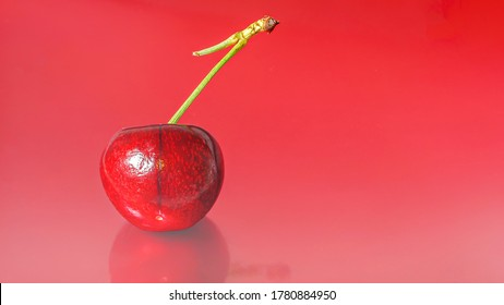 A single cherry on a red,relective background.