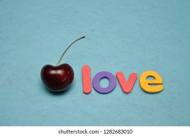 A single cherry with the word love