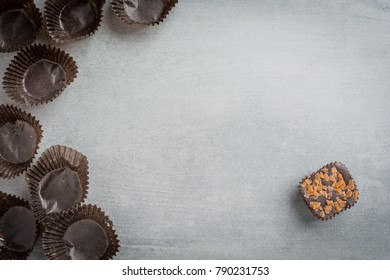 Single chocolate and empty wrappers on a stone background