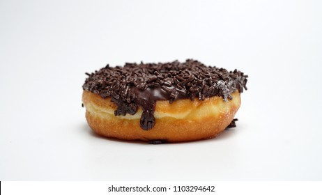 A single chocolate glazed donut with chocolate chips isolated white background top view