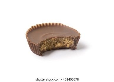A single chocolate peanut butter cup with a bite taken out of it, isolated on white with shadow