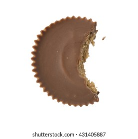 A single chocolate peanut butter cup overhead with a bite taken out of it, isolated on white.