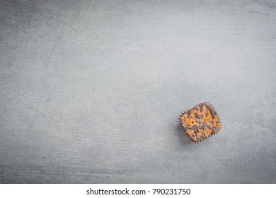 Single chocolate treat over a stone background
