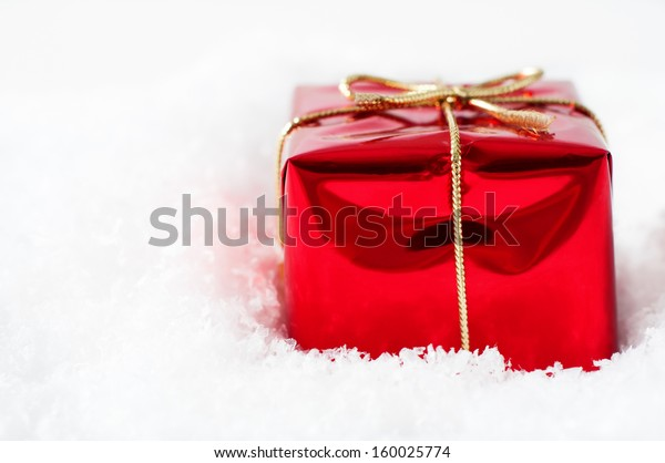 A single Christmas gift box in shiny red foil wrapping and tied to a bow with gold string ribbon, nestled in artificial white snow with copy space to the right.