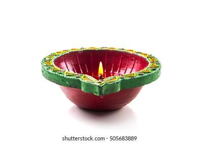 Single Clay diya lamp lit during diwali festival. Happy Diwali Greetings Card Design, Indian Hindu Festival of Lights called Diwali.