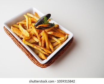A single common mussel on top of homemade golden french fries, white background