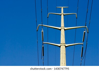 Single concrete electrical tower with cables and insulators off-center against blue sky.