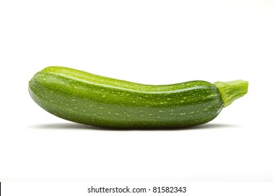 Single Courgette or zucchini from low perspective isolated on white.