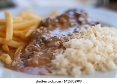 Single course with pork filet with mushrooms sauce, chips and rice.