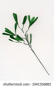 Single crepe paper mistletoe on white wooden background