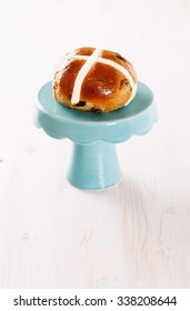 Single cross-bun on a cake stand over white wooden background. Selective focus