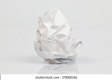 Single crumpled sheet of paper on neutral background