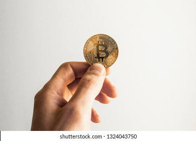 Single cryptocurrency bitcoin hold in hand on white background