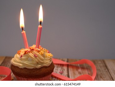 A Single Cupcake With Two Candles Lit Star Decorations And Pink Ribbon