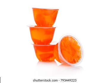 Single cups with mandarins in fruit jelly on white background
