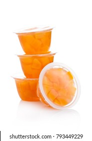 Single cups with peach in fruit jelly on white background