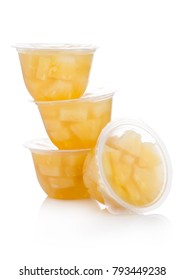 Single cups with pineapples in fruit jelly on white background