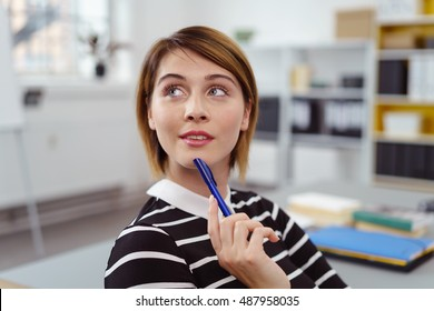 Single curious woman in striped black and white shirt with grin and pen on chin. She is looking up and over. Includes copy space.
