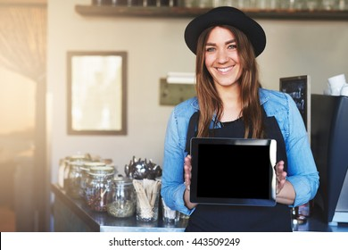 Single cute coffee house worker in hat and apron with cheerful expression holding blank tablet computer near counter