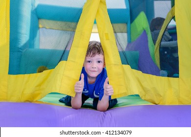 Single cute little curious boy with sweaty face looking from entrance of bouncy house