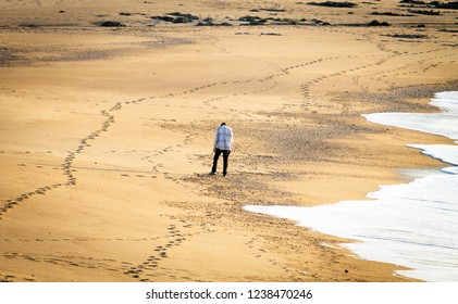 Single desolate lonely abandoned man stands in the sand near the incoming ocean tide. Marked footprints.