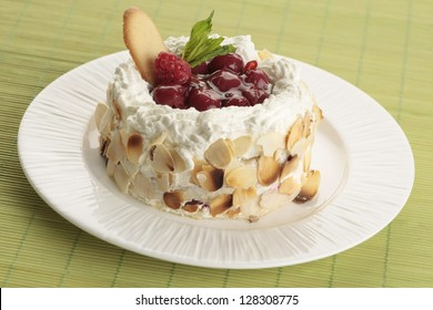 Single dessert with whipped cream and fruits on a white plate