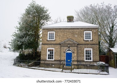 Single detached Victorian house with blue front door and small garden in the front during winter heavy snowing. Roof and garden covered in snow.