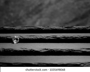 A Single Diamond Displaying the Facet Cut of the Stone, Laid on Slate Steps Leading up to a Rock Blurred Background