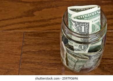 single dollar bills in glass mason jar on wood
