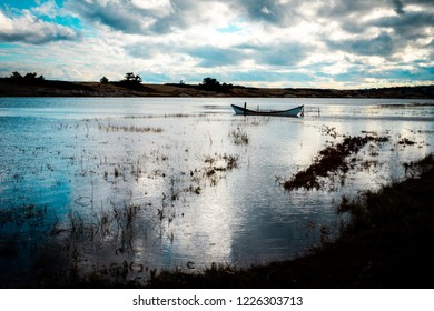 A single dory boat floats moored in the Ogunquit River surrounded by dunes and sea grass at high tide backlit by the setting sun.