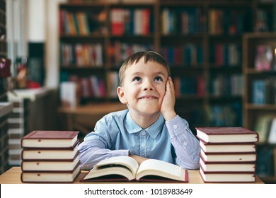 Single dreaming boy at the desk in the library enjoy books. Front image with boy keeping left hand on the cheek . European boy explore books. Pupil loves lecture, education, preparing for school.