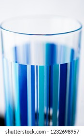 A single drinking glass with blue stripes in shallow depth of field