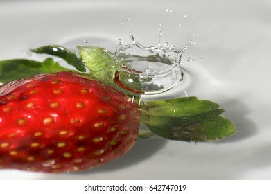 Single droplet of water falling into a tray of water with a strawberry