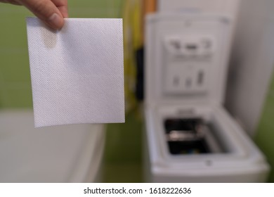 Single dryer sheet with waching machine in the background
