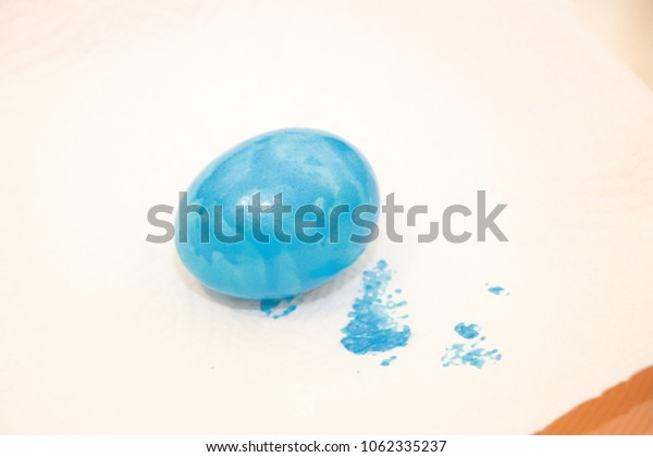 Single egg painted in shiny blue color on paper serviette with color spots on the edge . Dye eggs on easter.