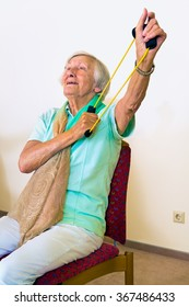 Single elderly woman in chair using elastic stretching bands to strengthen her shoulders and arms